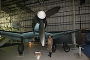 Flugzeugführerfigur als Größenvergleich neben der Luftschraube mit weißem Spinner