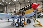 Aufgebockte Curtiss P-40 F 'Kittyhawk' X-17 bei Wartungsarbeiten im Hangar des IWM Duxford