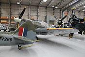 Supermarine Spitfire, Curtiss P-47 G 'Thunderbolt', Grumman F8F-2P 'Bearcat' und North American P-51 'Mustang' dicht gedrängt im Hangar des IWM stehend