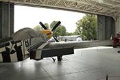 Blick über die rechte Tragfläche der P-51D 'Ferocious Frankie' durch das geöffnete Tor eines historischen RAF-Hangars